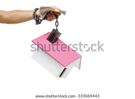 hand holding a pile of banknote and chained with a house - stock photo
