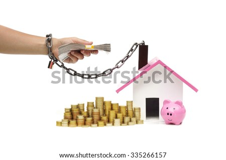 hand holding a pile of banknote and chained with a house - burden and debts of buying a new house concept - stock photo
