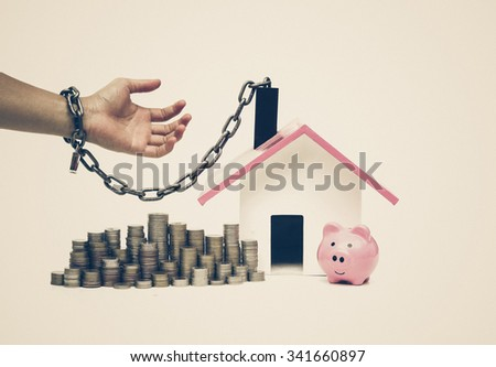hand holding a pile of banknote and chained with a house - burden and long term debts of buying a new house concept - stock photo