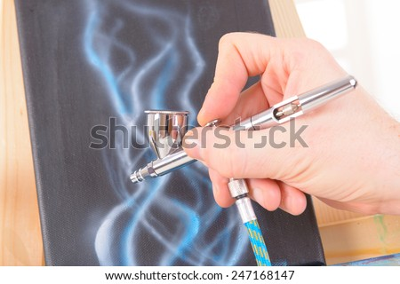 Hand holding a professional airbrush and painting - stock photo