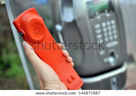 Hand holding a red handset of a public telephone - stock photo