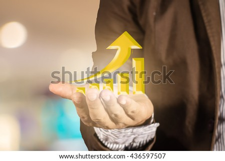 Hand holding a rising arrow representing growth / business concept in abstract bokeh background - stock photo
