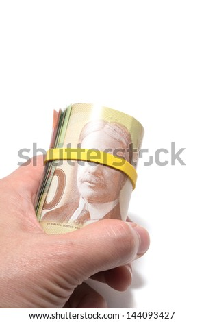 Hand holding a roll of bank notes with yellow plastic band over the eyes - stock photo