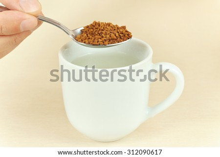Hand holding a spoon with granulated coffee over the cup of water - stock photo