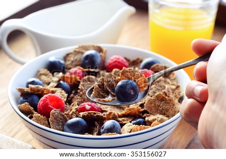 Hand holding a spoonful of bran flakes with blueberry, orange juice and milk jug in the background  - stock photo