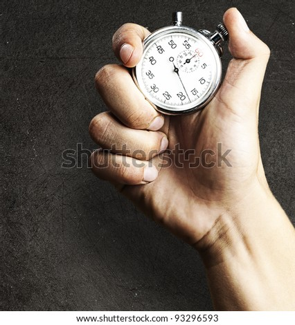 hand holding a stopwatch against a grunge background - stock photo