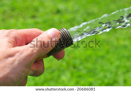 Hand holding a water hose - stock photo