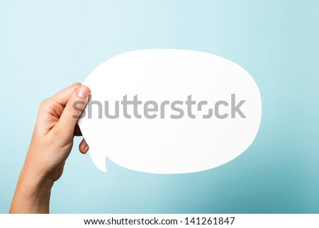 Hand holding a white blank speech bubble on blue background. - stock photo
