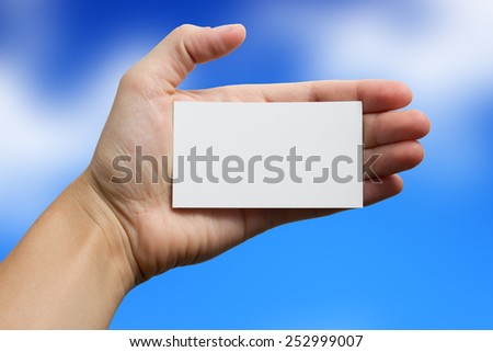 Hand holding a white business card on blue sky background  - stock photo