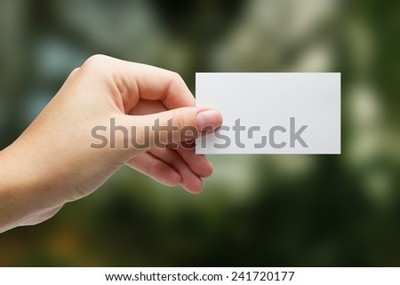 Hand holding a white business card on blurred green background - stock photo