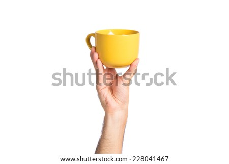 hand holding a yellow coffee cup over white - stock photo