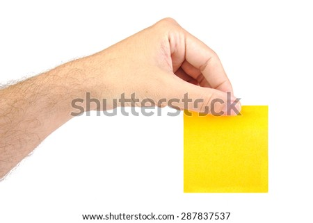 Hand holding a yellow notepaper or post it isolated on white  background - stock photo