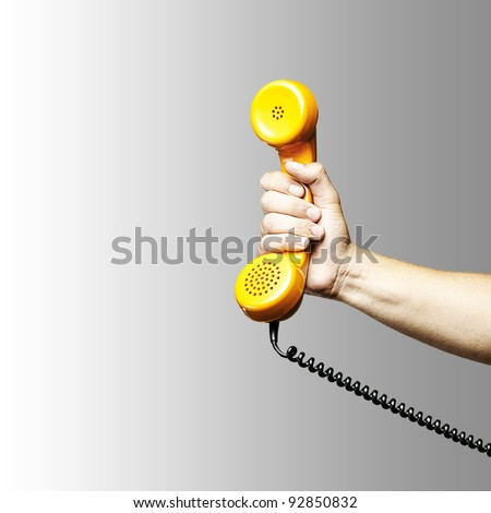 hand holding a yellow vintage telephone over grey background - stock photo