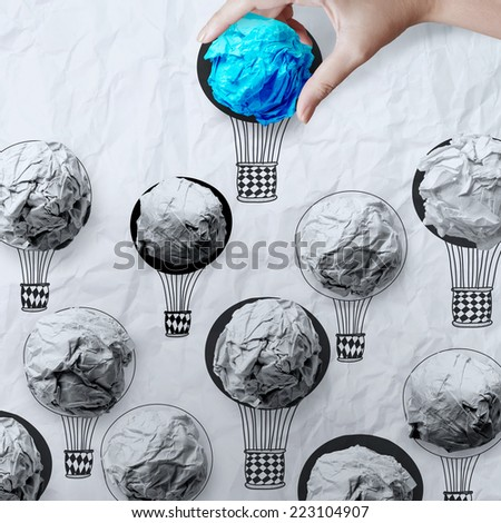 hand holding air balloons with crumpled paper ball as leadership concept - stock photo