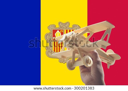Hand holding airplane plane over Andorra flag, travel concept - stock photo