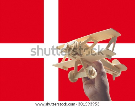 Hand holding airplane plane over Armenia flag, travel concept - stock photo