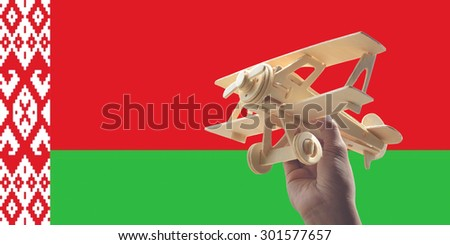 Hand holding airplane plane over Belarus flag, travel concept - stock photo