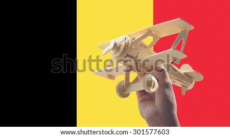 Hand holding airplane plane over Belgium flag, travel concept - stock photo