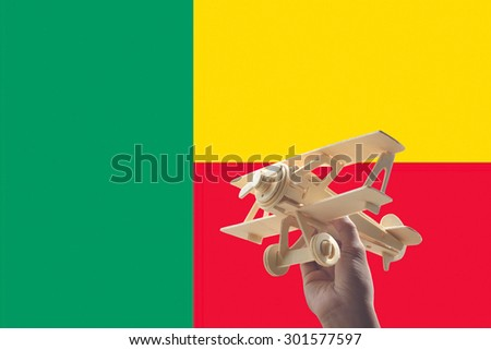 Hand holding airplane plane over Benin flag, travel concept - stock photo