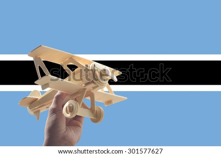 Hand holding airplane plane over Botswana flag, travel concept - stock photo