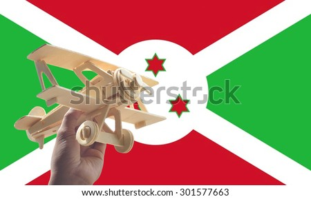 Hand holding airplane plane over Burundi flag, travel concept - stock photo