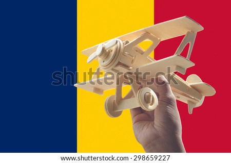 Hand holding airplane plane over Chad flag, travel concept - stock photo