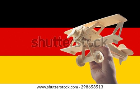 Hand holding airplane plane over Germany flag, travel concept - stock photo