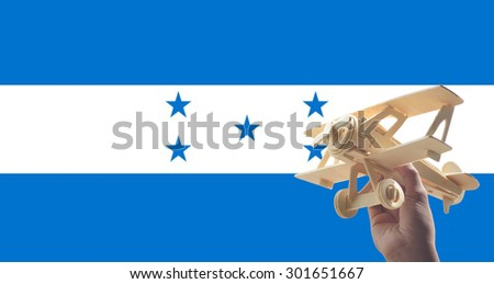 Hand holding airplane plane over Honduras flag, travel concept - stock photo