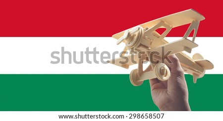 Hand holding airplane plane over Hungary flag, travel concept - stock photo