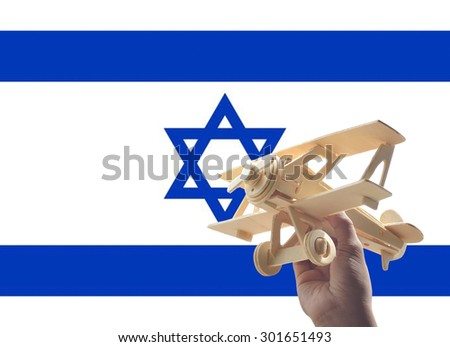 Hand holding airplane plane over Israel flag, travel concept - stock photo
