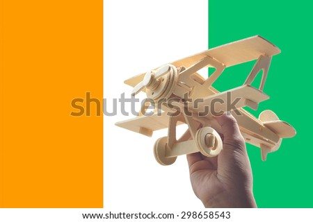 Hand holding airplane plane over Ivory Coast, travel concept - stock photo