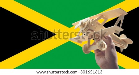 Hand holding airplane plane over Jamaica flag, travel concept - stock photo