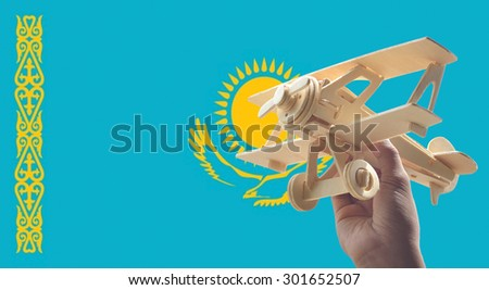 Hand holding airplane plane over Kazakhstan flag, travel concept - stock photo