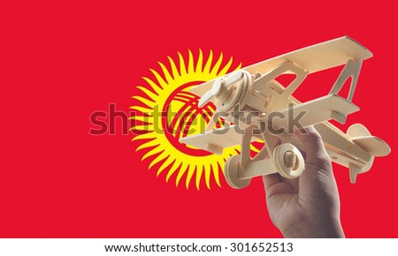 Hand holding airplane plane over Kyrgyzstan flag, travel concept - stock photo