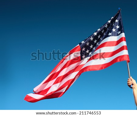 Hand holding american flag on the blue sky background - stock photo