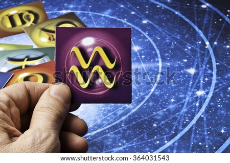 hand holding an astrology card with symbol of sign of Aquarius - stock photo