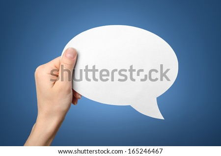 Hand holding an empty speech bubble on blue background - stock photo