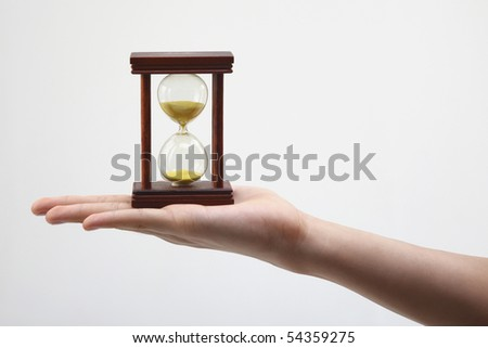hand holding an hour glass on the plin background - stock photo