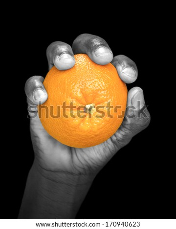 Hand holding an orange - partially monochrome - stock photo