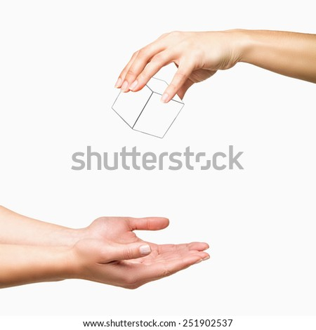 Hand holding and dropping white cube to other hand on white background - stock photo