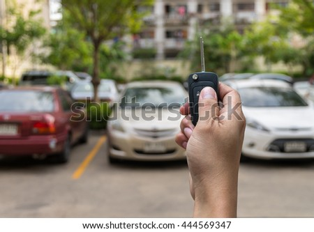 Hand holding and touching the keys over photo blurred of used car for open the door car, transportation and ownership concept - stock photo