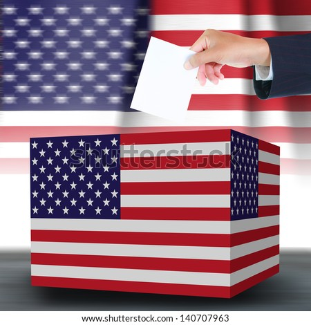 Hand holding ballot and box with the USA flag in the background - stock photo