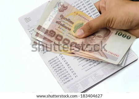 Hand holding banknote and bank book isolated on white - stock photo