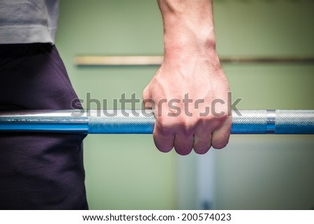Hand holding barbell - stock photo