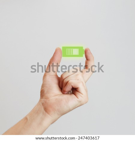 Hand holding battery icon, Male hand holding green battery  - power concept - stock photo