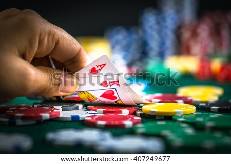 Hand Holding Best Deal Game Cards and Money Chips - stock photo