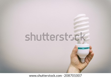 Hand holding big energy efficient spiral-shaped fluorescent lamp. - stock photo