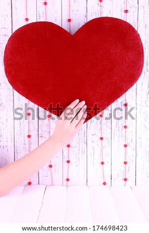 Hand holding big red heart on wooden background - stock photo
