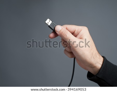 Hand holding black USB cable - stock photo