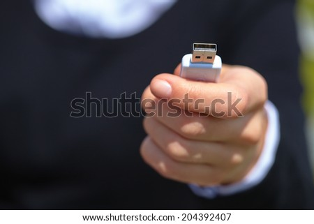hand holding black USB data storage - stock photo